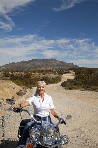 Senior woman riding motorcycle on desert road