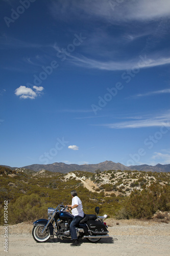 Senior man riding motorcycle on desert road looking to mountains in background