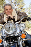 Senior man leaning on motorcycle handlebars