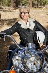 Senior woman sits on motorbike with forest in background