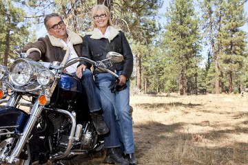 Senior couple lean on motorcycle in forest