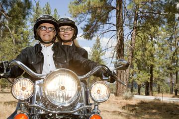 Senior couple riding motorcycle through a forest