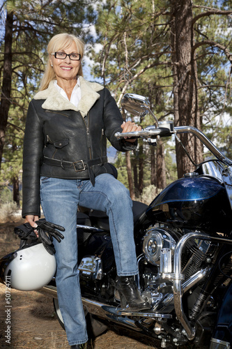 Senior woman in leather jacket poses with motorcycle