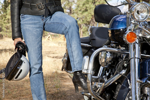 Womans leg rests on motorcycle foot rest