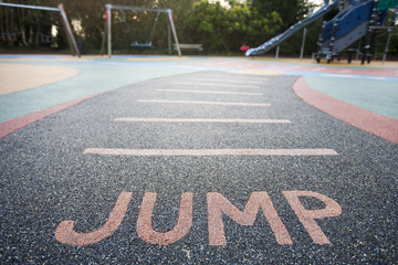 """Jump"" written into rubber floor of playground"