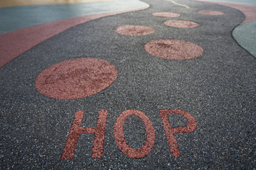 """Hop"" written into rubber floor of playground"