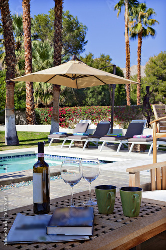 Wine and wineglasses by poolside