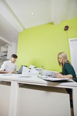 Side view of young businesspeople busy working at desk