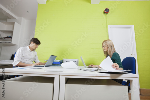 Side view of young businesspeople busy working in office