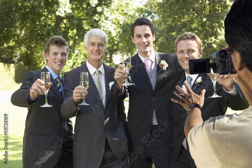 Man taking a picture of five men toasting with wine glasses at wedding party