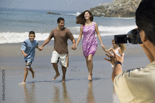 Man video recording happy Hispanic Latin family walking at beach