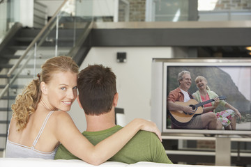 Portrait of young Caucasian woman with man watching movie on television in living room