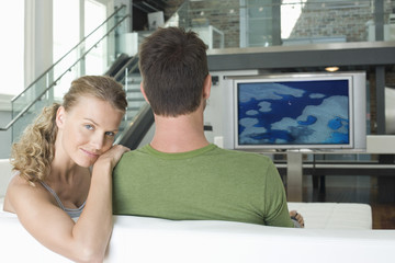 Portrait of young Caucasian woman with man watching television in living room