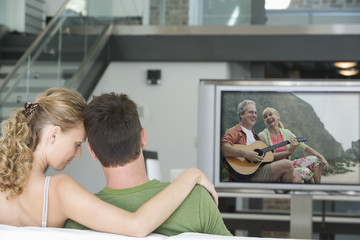 Rear view of young couple watching television in living room