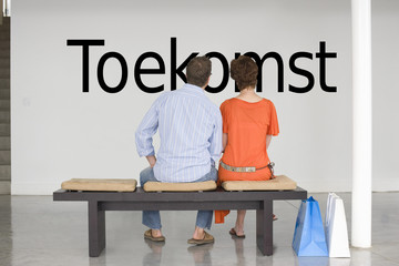 "Rear view of couple seated on bench reading Dutch text ""Toekomst"" (future) on wall"