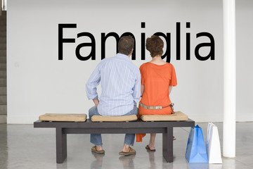 """Rear view of couple seated on bench reading Italian text """"Famiglia"""" (family) on wall"""