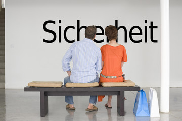"Rear view of couple reading German text ""Sicherheit"" (security) and contemplating about security"