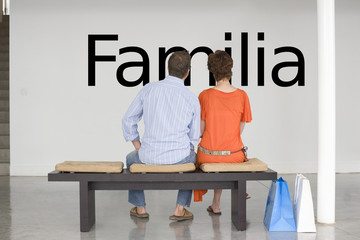 "Rear view of couple seated on bench reading Spanish text ""Familia"" (family) on wall"