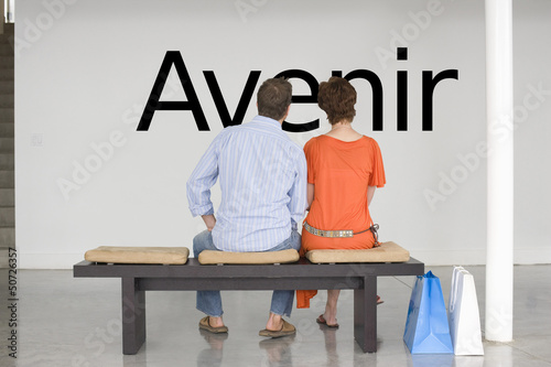 "Rear view of couple seated on bench reading French text ""Avenir"" (future) on wall"