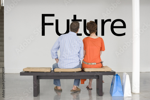 Rear view of couple seated on bench reading English text on wall
