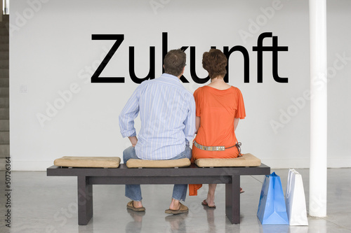 "Rear view of couple seated on bench reading German text ""Zukunft"" (future) on wall"