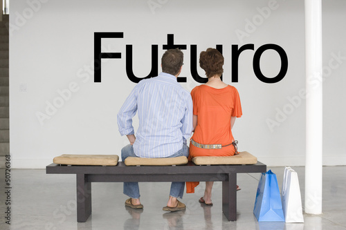 "Rear view of couple seated on bench reading Spanish text ""Futuro"" (future) on wall"