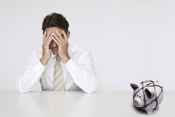 Worried businessman at table with trapped piggy bank representing financial difficulties