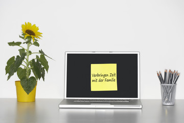 "Sunflower plant on desk and sticky notepaper with German text on laptop screen saying ""Verbringen Zeit mit der Familie"""