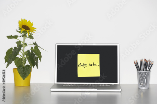 "Sunflower plant on desk and sticky notepaper on laptop screen with ""einige Arbeit"" written on it in German"