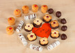 Sweet cookies with valentine card on wooden background