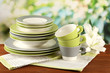 Empty plates and cups on wooden table on green background