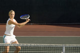 Young female tennis player swinging racket at court