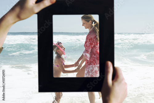 Female hands framing mother and daughter playing in water at beach