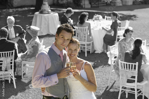Portrait of newly wedded couple with champagne glasses at wedding reception