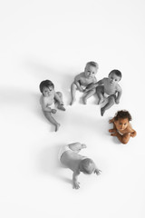 High angle view of baby girl looking up with other babies sitting on floor
