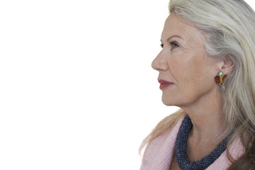Side view of pensive senior woman against white background