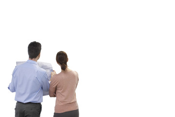 Rear view of businesspeople holding blueprint against white background