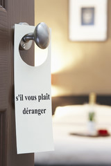 "Sign with French text ""s'il vous plait deranger"" (please disturb) hanging on hotel room door"