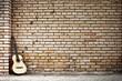 chitarra poggiata su muro di mattoni