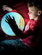 Zukunft Erde - Kind betrachtet einen Globus im Dunkeln