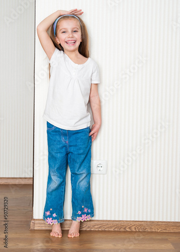 little girl measures the growth