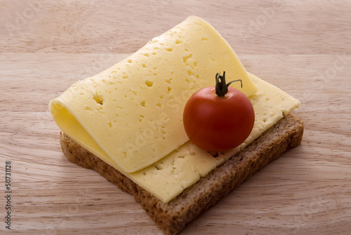 open cheese sandwich with tomato on wooden chopping board