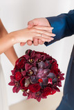 Hands with wedding rings and bouquet. happy newlyweds