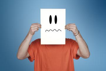 garçon montrant un papier blanc avec un émoticône