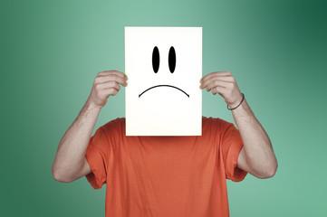 garçon montrant un papier blanc avec un émoticône triste