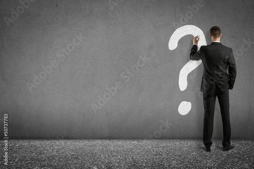 businessman painting question mark on wall