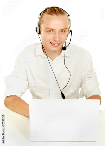 A young businessman with a headset in front of a laptop