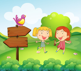 A wooden board with a bird beside the two young girls