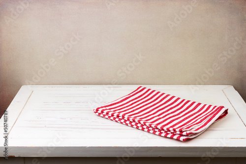 Background with white wooden table and red striped tablecloth