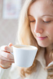 Coffee. Beautiful young woman holding in hand a cup of coffee